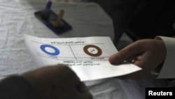 "A man marks ""disagree"" on his ballot while voting during a referendum on the new Egyptian constitution."