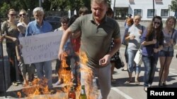 """Активисты украинской организации """"Наступ"""" сжигают изготовленные в России продукты в знак протеста против торговой войны Москвы. 16 августа 2013 года."""
