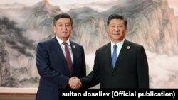 Қырғызстан президенті Сооронбай Жээнбеков (сол жақта) пен Қытай президенті Си Цзиньпин. Циндао, 10 маусым 2018 жыл.