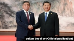 Then-Kyrgyz President Sooronbai Jeenbekov (left) and Chinese President Xi Jinping met on the sidelines of the Shanghai Cooperation Organization summit in Qingdao in June 2018.