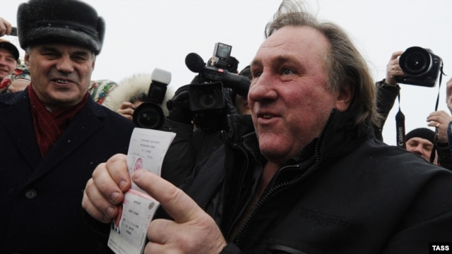 French actor Gerard Depardieu shows off his Russian passport after arriving at the airport in Saransk in Russia's Mordovia region on January 6.