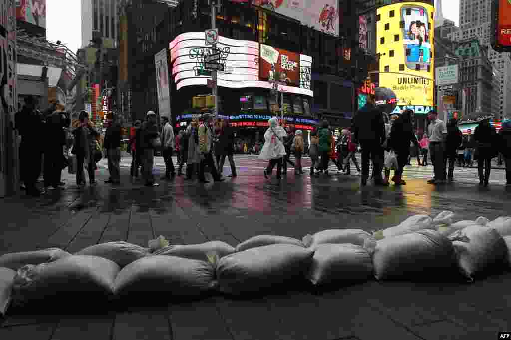 People walk by sand bags in front of a building in Times Square as Hurricane Sandy begins to affect the area in New York City.