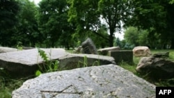 Gravestones from a destroyed Jewish cemetery near a monument to Jews killed during World War II