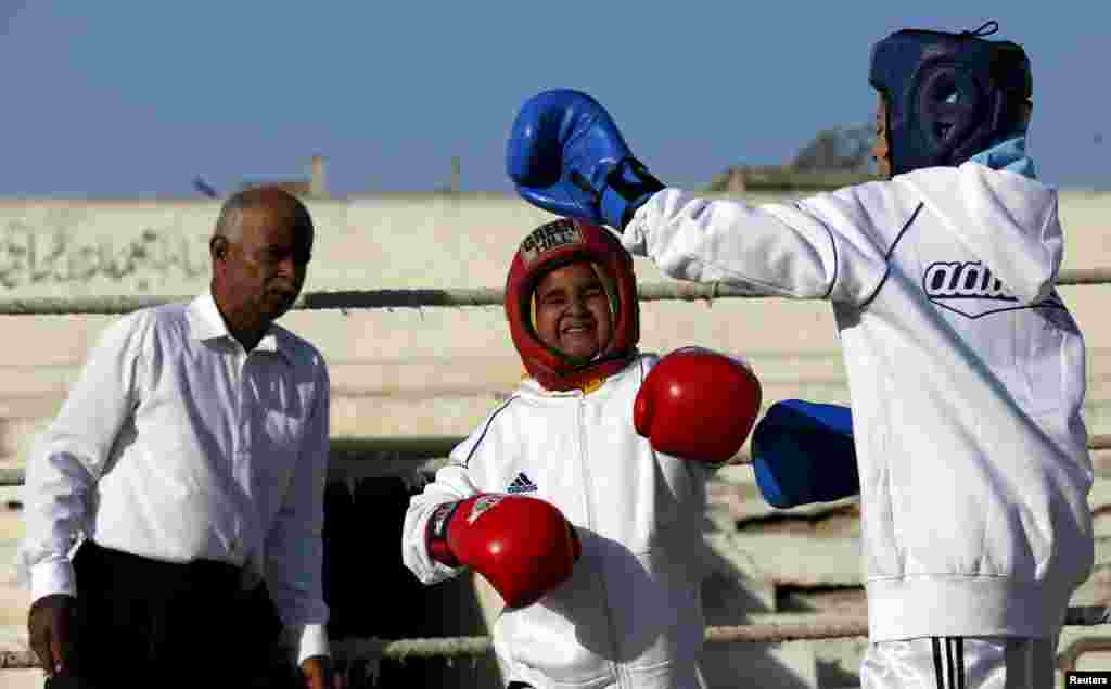 Tabia (R), 12, fights against Aamna, 11, during the Sindh Junior Sports Association Boxing Tournament in Karachi.