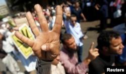 """""""Мұсылман бауырлар"""" қозғалысының жақтаушылары Каир көшелерінде жаңа символды көрсетіп жүр. 23 тамыз 2013 жыл."""