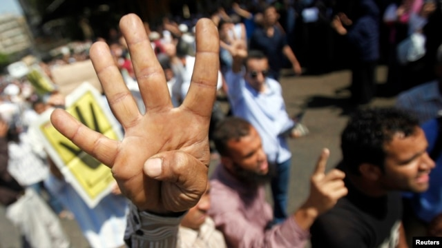 "Supporters of Egypt's Muslim Brotherhood shout slogans against the military and the Interior Ministry as they gesture ""Rabia"" or ""Four"" during a protest in front of Al-Tawhid Mosque, which leads to Ramses Square in Cairo on August  23, 2013."