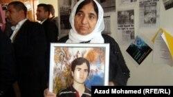 سيدة تحمل صورة لولدها اللاجئ الذي إنتحر بعد عودته
