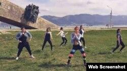 Кадр видеозаписи о танце девушек на фоне мемориала «Малая земля».