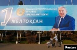 Қазақстан президенті Нұрсұлтан Назарбаевтың бейнесі бар жарнама тұрған жерден өтіп бара жатқан әйел. Алматы, 30 қараша 2015 жыл.