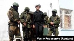 Украинский военно-морской офицер покидает военно-морской штаб ВМС Украины в Севастополе, окруженный российскими военными, 14 марта 2014 года
