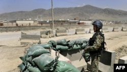 An Afghan soldier stands guard at the gate of an air-force compound in Kabul in April 2011.