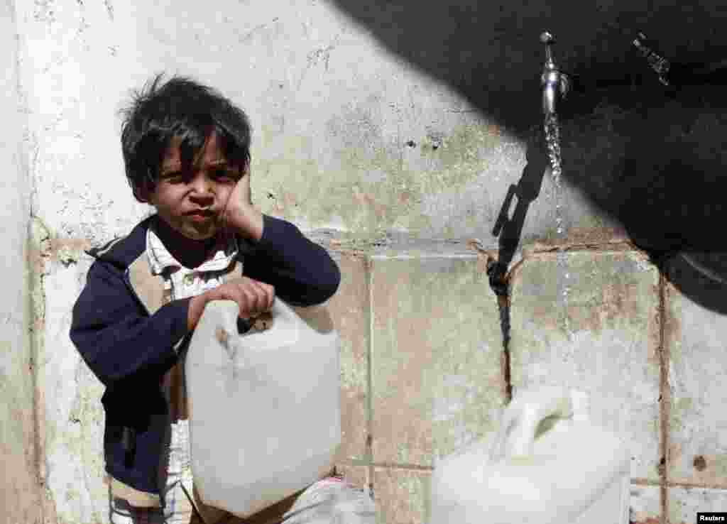 A Yemeni boy fills up a jug of water in Sanaa where water supplies are under considerable strain. (Reuters/Mohamed al-Sayaghi)