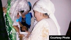 Shahnoza Idrisova (left) and her new mother-in-law perform a wedding ritual during her Internet nuptials last month.