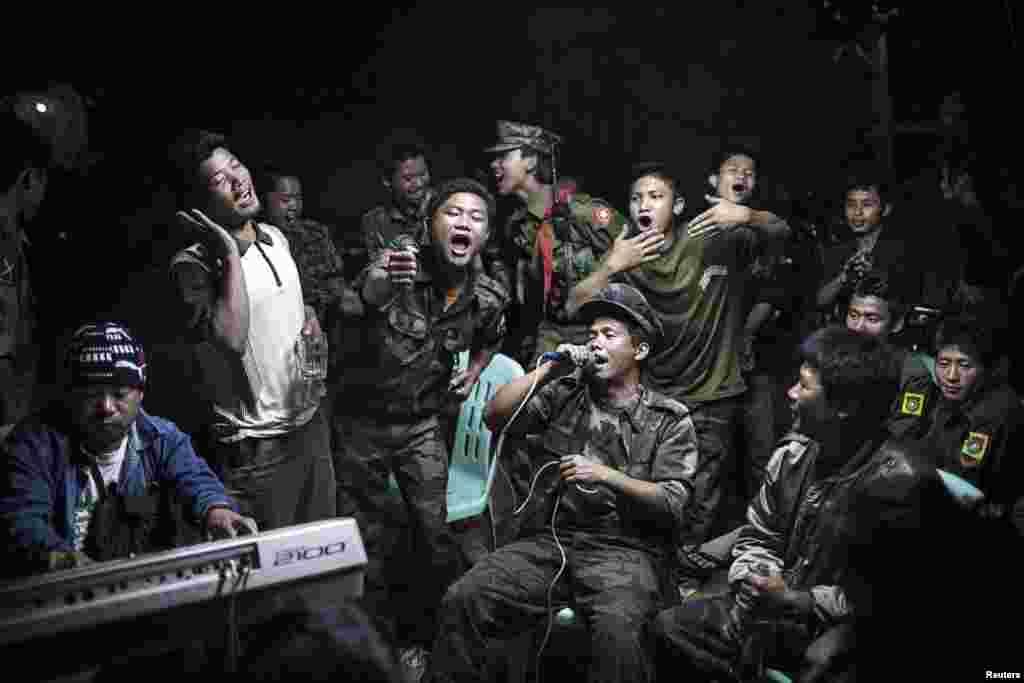 """Һолландиянең De Volkskrant газеты өчен эшләүче алман фотографы Юлиус Шранк шушы фотосы белән """"Ялгыз фотода көндәлек тормыш"""" номинациясендә җиңде. Фотодан Бирмадан аерылу өчен сугышучы Качин бәйсезлек армиясе сугышчылары үзләренең бер җитәкчеләренең җеназасында җырлый."""