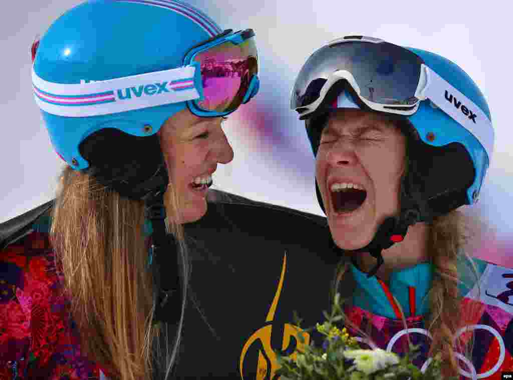 Silver medalist Anke Karstens (left) of Germany shares a laugh with bronze medal winner Amelie Kober of Germany during the flower ceremony for the women's snowboard parallel slalom. (epa/Jens Buettner)
