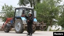 Полицейский блокирует улицу на месте спецоперации против подозреваемых боевиков. Актобе, 10 июня 2016 года.