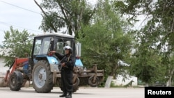 A Kazakh police officer blocks a street near the site of an exchange between Kazakh security forces and suspected militants linked to deadly attacks this week on a national guard base and several firearms shops, in Aqtobe, on June 10.