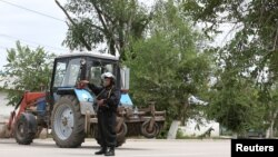 A Kazakh police officer blocks a street near the site of a fire exchange between Kazakh security forces and suspected militants linked to deadly attacks on a national guard base and several firearms shops in the city of Aqtobe in June.