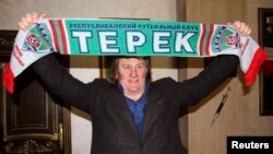 Actor Gerard Depardieu holds up a scarf of Terek Grozny soccer club as he poses for a picture during a visit to the Akhmat-Arena sports stadium in Grozny in February 2013.
