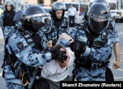 Riot police forcibly detain a protester in Moscow on July 27.