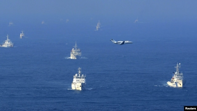 Chinese ocean surveillance, fishery patrol ships, and a Japan Coast Guard patrol ship (right) all sail about 15 kilometers west of the disputed islands, in the East China Sea, on September 18.