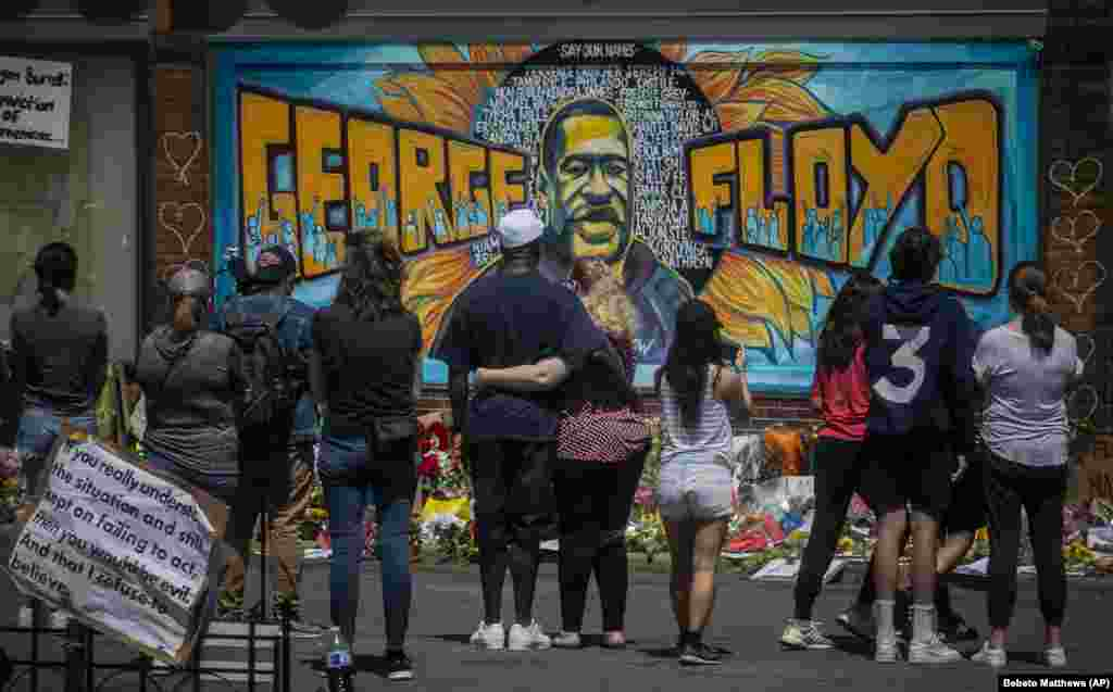 Visitors make silent visits to organic memorial featuring a mural of George Floyd, near the spot where he died while in police custody, Sunday May 31, 2020, in Minneapolis, Minn. (AP Photo/Bebeto Matthews)