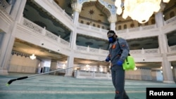 A specialist wearing a protective mask sprays disinfectant as he sanitizes the Moscow Cathedral Mosque to prevent the spread of coronavirus in Moscow on March 27.