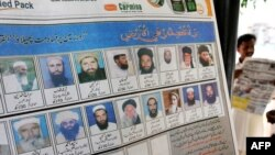 A newspaper featuring mugshots of radical cleric Maulana Fazlluah and other militants hangs on a tree at a roadside stall in Islamabad.