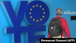 """A man walks past a """"Vote"""" sign at the an station near the European Parliament in Brussels on May 24."""