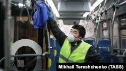 Сотрудник в защитной маске дезинфицирует автобус. Москва, март 2020 года.