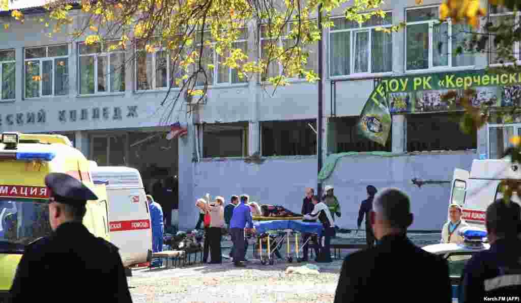 Спасатели несут жертву взрыва в колледже.