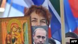 A Kosovo Serbian woman holds a religious icon and portrait of Russian leader Vladimir Putin during a protest in Mitrovica in February 2008.
