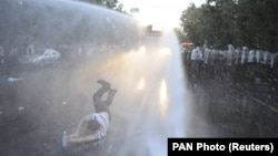 Armenia -- A protester is hit by a jet of water released from a riot police vehicle during a rally against a recent decision to increase the tariff on electricity, in Yerevan, Armenia, June 23, 2015.
