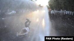 Струи из полицейского водомета сбивают с ног участника протеста в Ереване, 23 июня 2015 года