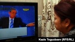 """Жительница Алматы смотрит программу на телеканале """"Хабар""""."""