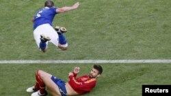 Испандық футболшы Херард Пике (төменде) Италиялық ойыншы Тьяго Моттаға қарсы ойын ережесін бұзды. Польша, Гданьск, 10 маусым 2012 жыл.
