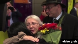 Leyla Yunus and her husband, Arif (right rear), were greeted by their daughter, Dinara Yunus