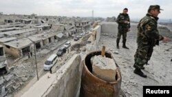 Forces loyal to Syrian President Bashar al-Assad stand atop of a building in a district of Aleppo that is now under government control.
