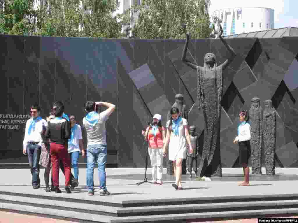 Астаналық белсенділер мойындарына көк орамал тағып, саяси қуғын-сүргін құрбандарының ескерткішіне тағзым етті. 31 мамыр 2013 жыл.
