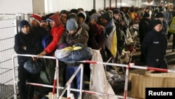 Беженцы стоят в очереди перед регистрацией в Берлине. 9 декабря 2015 года.