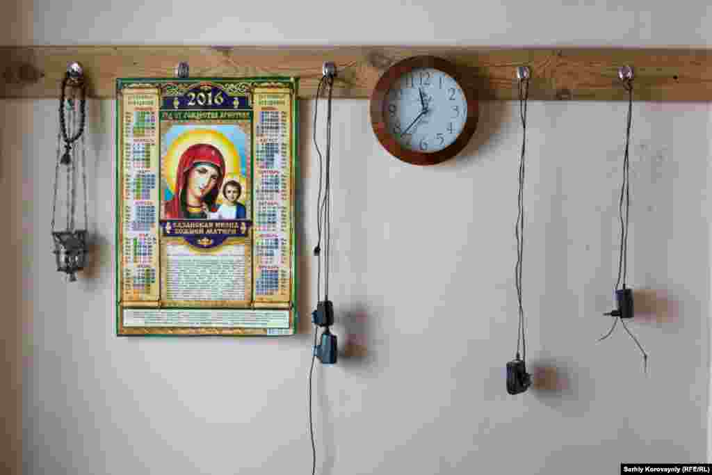 A calendar with the image of Mary hangs alongside mobile phone chargers in the monastery's living quarters.