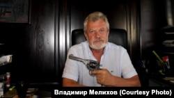 Владимир Мелихов держит в руках револьвер из коллекции музея