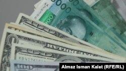 Банкноты кыргызского сома номиналом пять тысяч и американского доллара номиналом один и сто.
