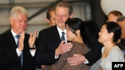 Former President Bill Clinton (left) and Vice President Al Gore greet freed journalists Laura Ling and Euna Lee (right) upon their arrival in the United States.