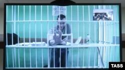 Россия, 17 февраля 2015 года, Олег Навальный (на экране по видеосвязи из СИЗО) перед рассмотрением жалобы защиты на приговор А.Навальному и О.Навальному по делу «Ив Роше».
