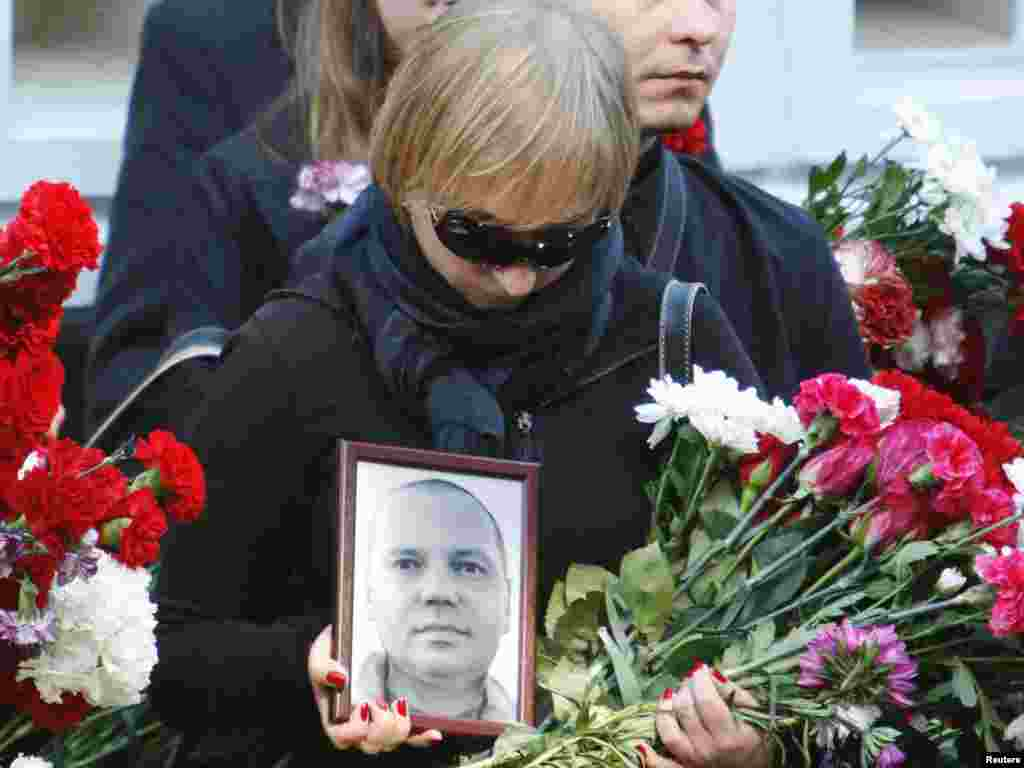 A woman carries a portrait of Belarusian journalist Aleh Byabenin during his funeral in Minsk on September 6. Belarus's opposition has rejected a police statement that the death of Byabenin, the director of one of the country's most prominent opposition media outlets, was suicide, saying he had no reason to kill himself. Photo by Vasily Fedosenko for Reuters