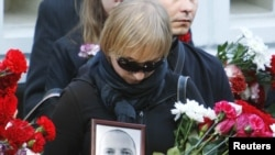 A mourner carries a portrait of Belarusian journalist Aleh Byabenin at his funeral in Minsk on September 6.