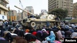 """Мубарактын режимине каршы чыккан демонстранттар Каирдин """"ат-Тахрир"""" аянтында танктардын жанында намазга жыгылышты. 2011-жылдын 11-февралы. REUTERS/Yannis Behrakis."""