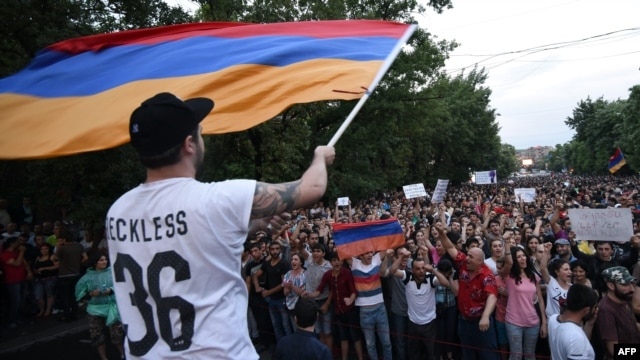 A demonstrator waves an Armenian flag as others shout slogans during a protest against an increase of electricity prices in Yerevan on June 25.