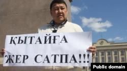 Активист Исатай Утепов стоит в центре Уральска с плакатом, призывающим не продавать землю Китаю. 24 апреля 2016 года.